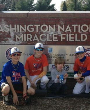 Three Miracle League Mo Co MD Buddies with Player at the Washington Nationals Miracle Field Sign