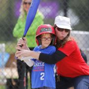 Volunteer coaching kid to swing bat